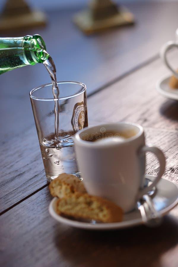 Gietende water en espresso stock foto's