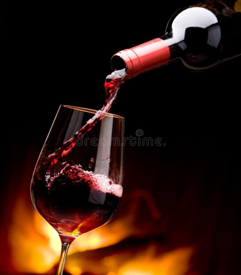 Gietende wijn door de open haard stock afbeelding