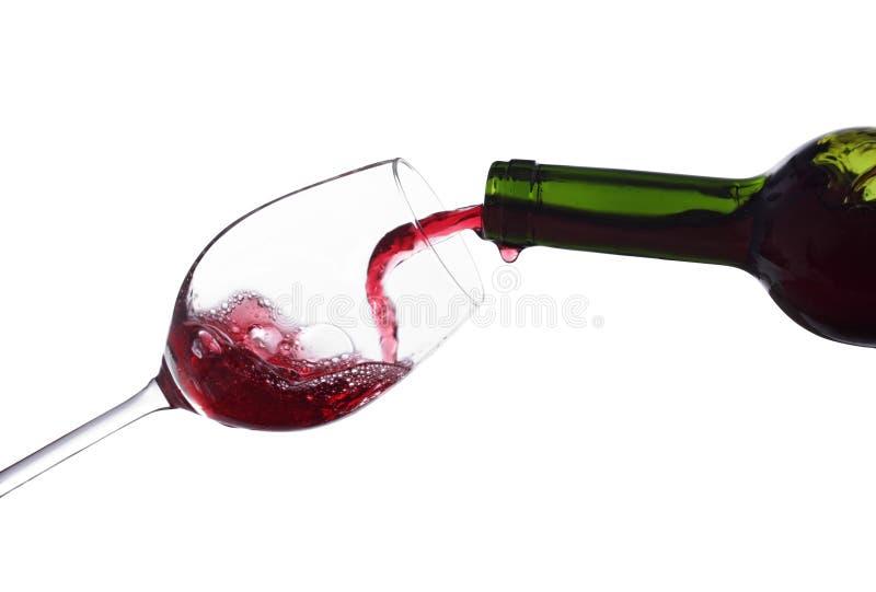 Gietende wijn in een geïsoleerdg glas stock foto's