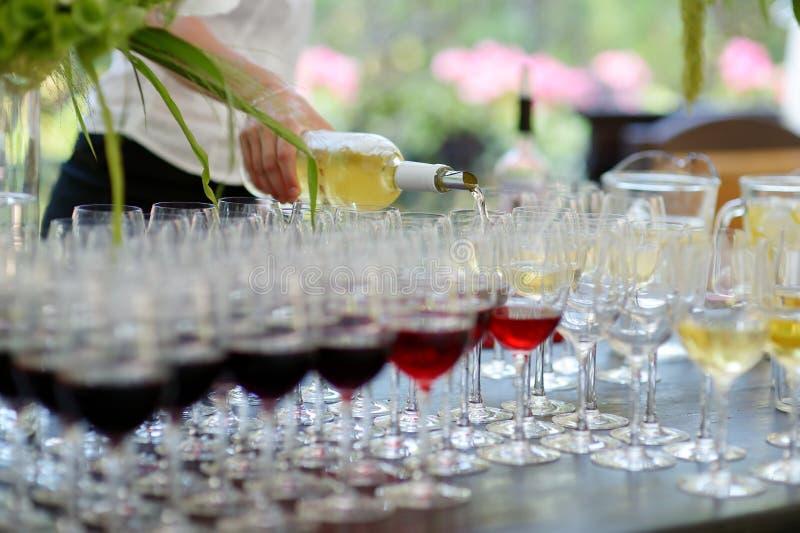 Gietende wijn in glazen stock afbeelding