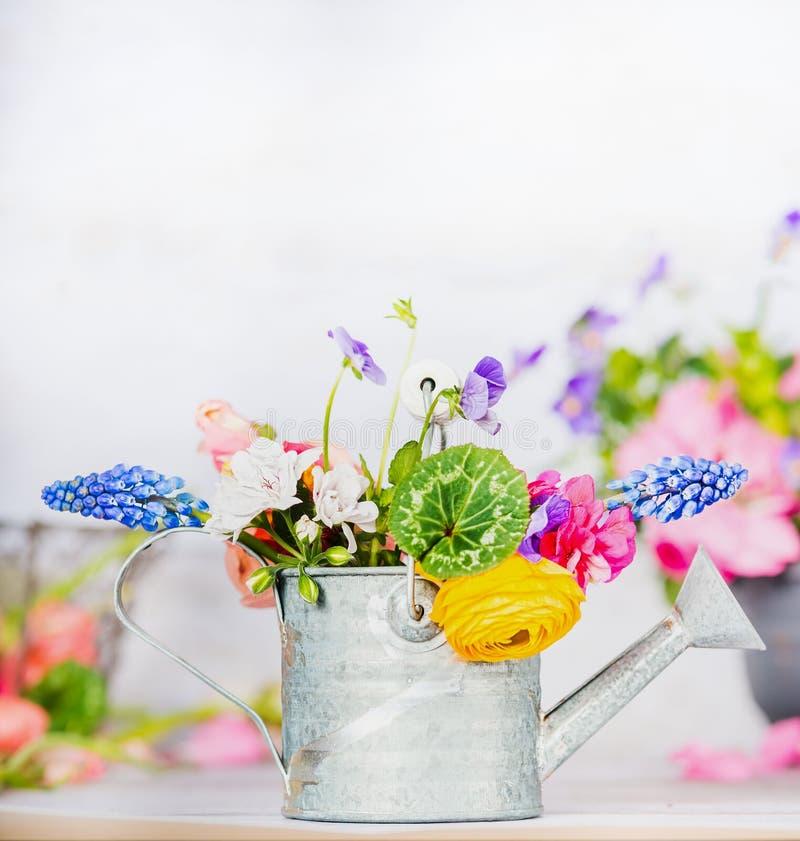 Gieter met kleurrijke tuinbloemen op lijst, vooraanzicht, het tuinieren stock afbeeldingen