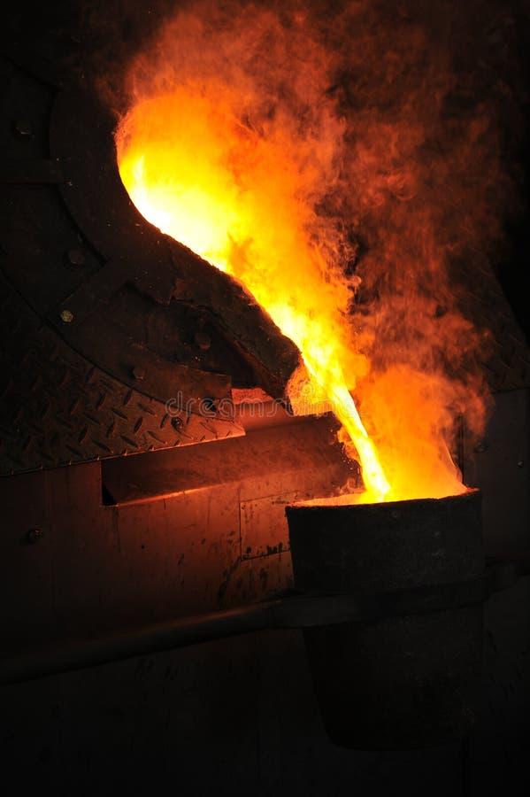 Gieterij - gesmolten metaal dat van gietlepel wordt gegoten royalty-vrije stock afbeelding