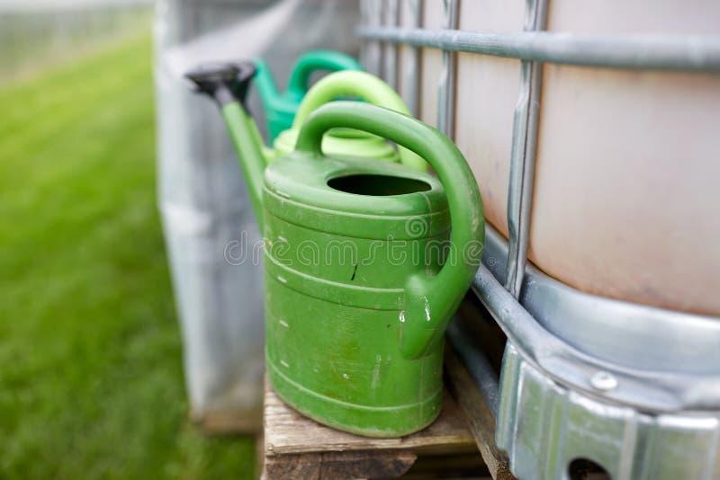 Gieters bij de tank van het landbouwbedrijfwater royalty-vrije stock fotografie