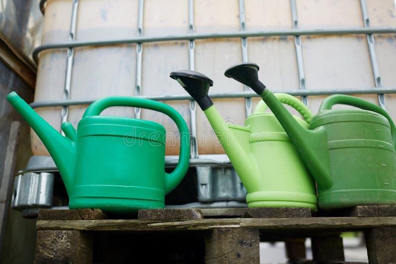 Gieters bij de tank van het landbouwbedrijfwater royalty-vrije stock foto