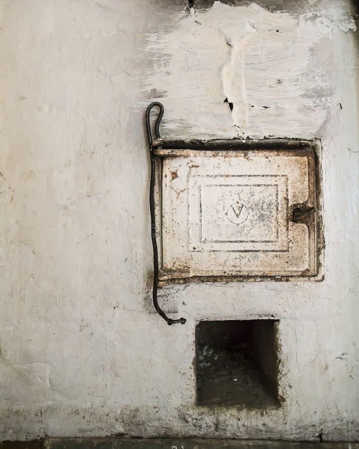 Gietijzerdeur en pook voor steenkool op een traditioneel, oud Russisch fornuis royalty-vrije stock foto