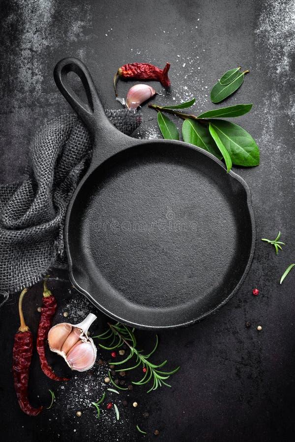 Gietijzerpan en kruiden op zwarte metaal culinaire achtergrond stock foto