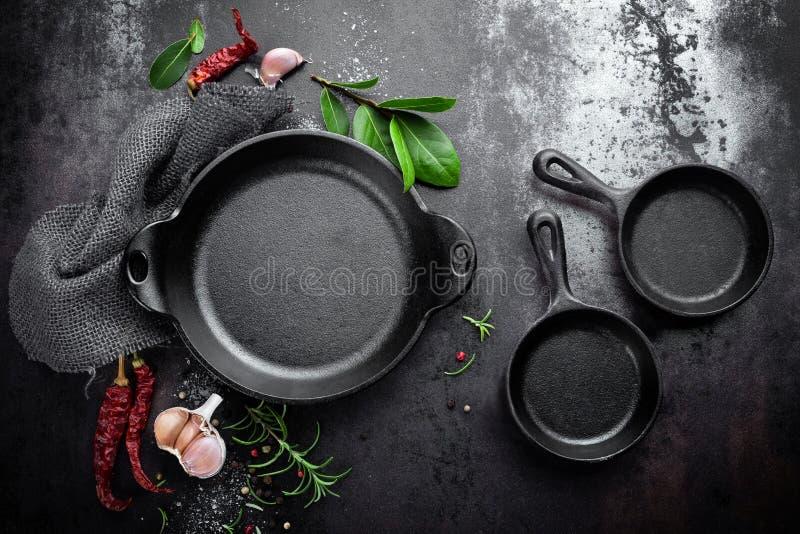 Gietijzerpan en kruiden op zwarte metaal culinaire achtergrond stock foto's
