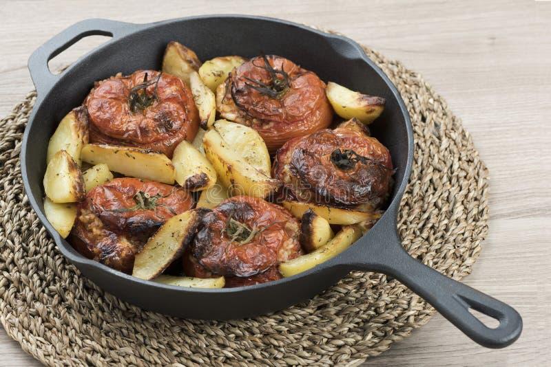 Gietijzerpan met tomaten met rijst en aardappelen in de schil royalty-vrije stock afbeeldingen