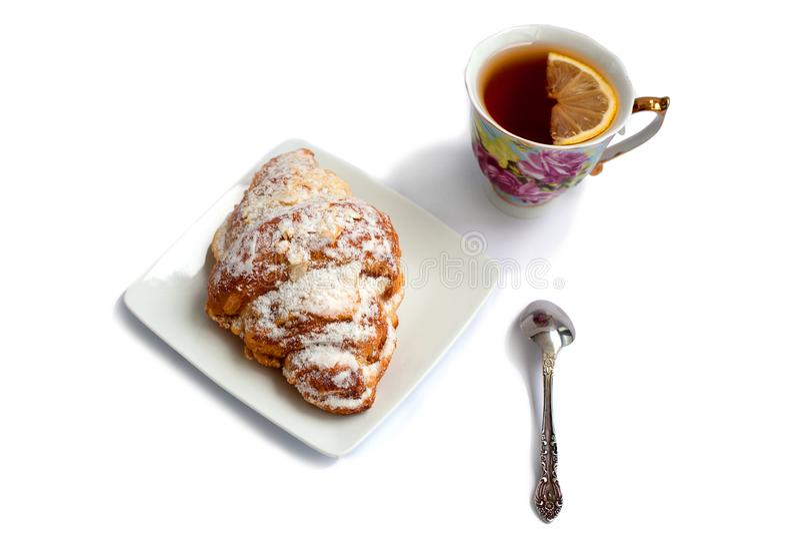 Giffel på en vit platta med en kopp te med citron- och efterrättskeden på en vit bakgrund royaltyfri bild