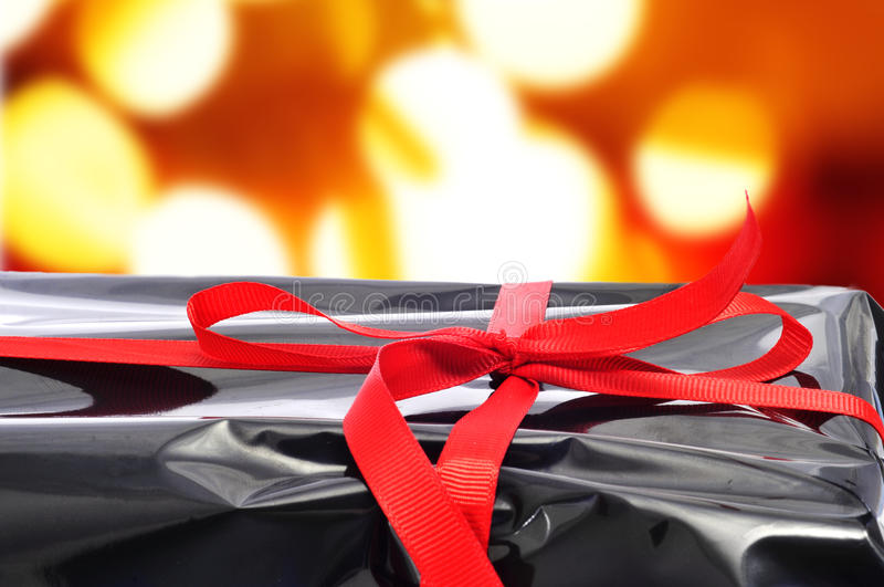 Gift. Closeup of a gift wrapped with black plastic and tied with red ribbon royalty free stock photo