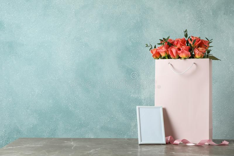 Gift bag with bouquet of pink roses and empty frame on grey table stock images