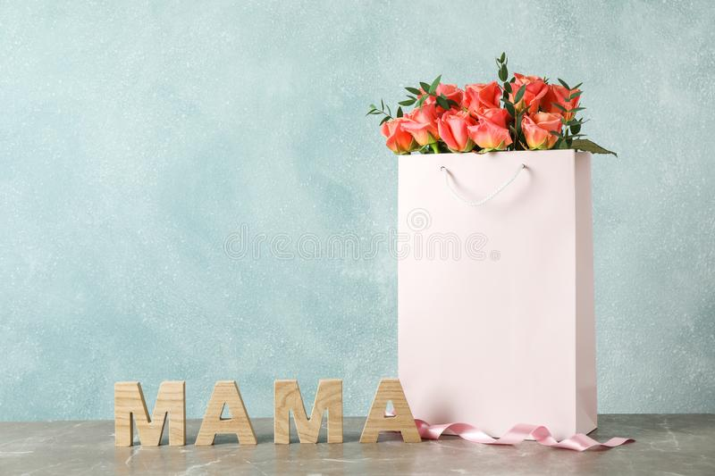 Gift bag with bouquet of pink roses and inscription Mom on grey table royalty free stock images