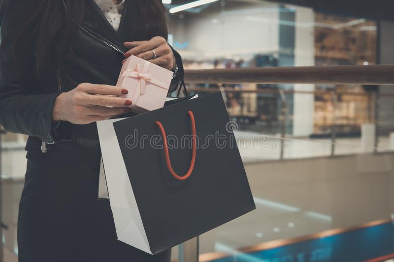 gift bags in the hands of the girl, on the background, Shopping Mall. shopping, gifts, sale, New Year's shopping. Woman puts a royalty free stock photo