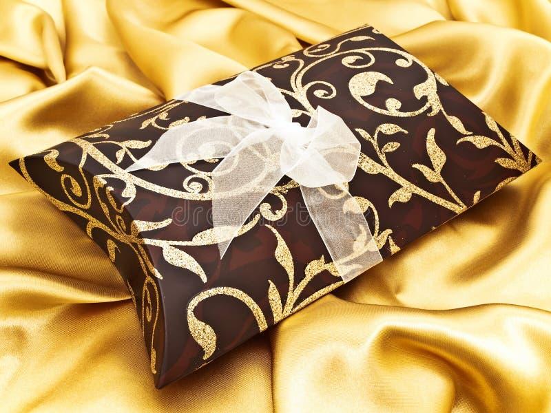 Gift bij gouden stof royalty-vrije stock afbeelding