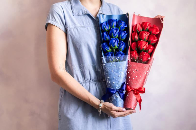Gift bouquet: Florist girl demonstrates blue and red rose bouquet. stock images