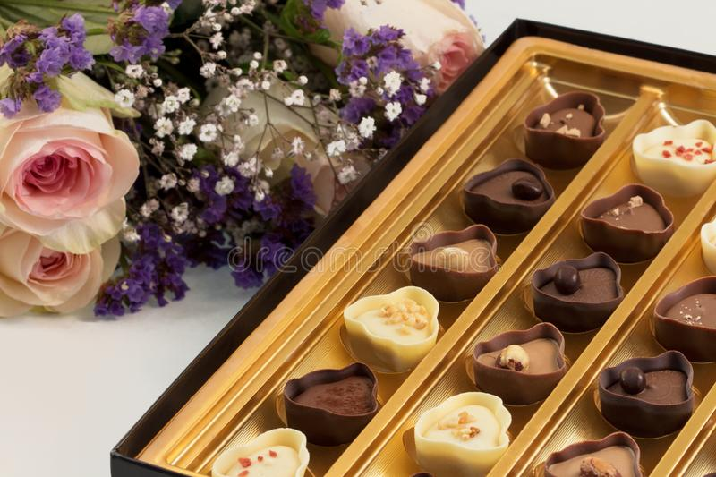 Bouquet of pink roses with baby breath and purple flowers next to fancy box of chocolates. stock photos