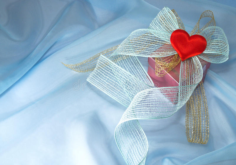 Gift with a bow and a heart. On blue organza to Valentine's Day royalty free stock images