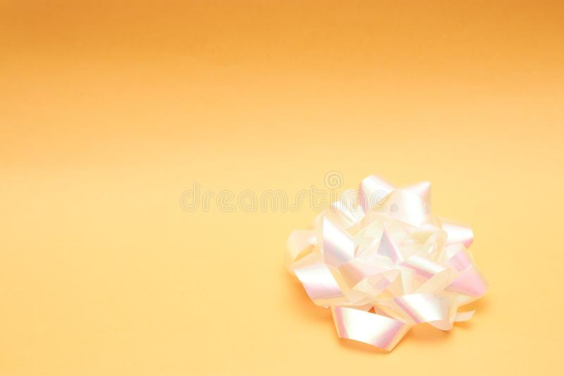 Gift bow from a light ribbon on a peach background. Copy space. postcard royalty free stock images