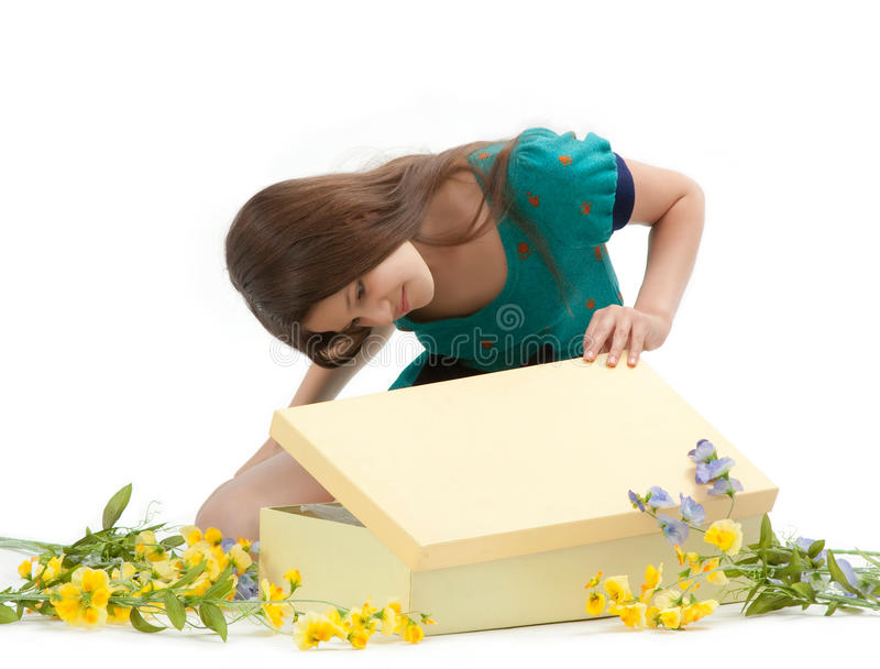 Gift Box. Cute young girl opens a gift box among the flowers on white background stock photos