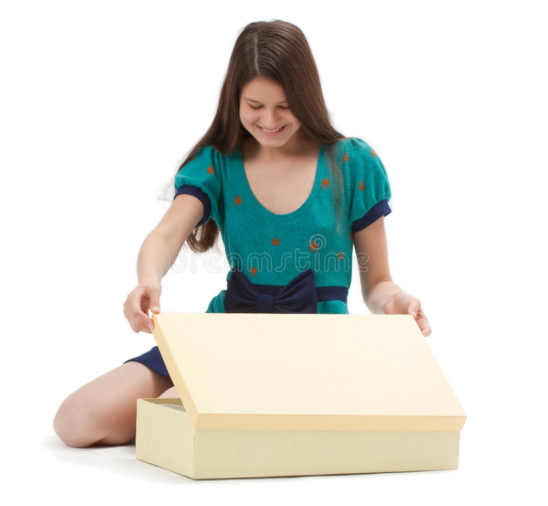 Gift Box. Cute young girl opens a gift box on white background stock photos