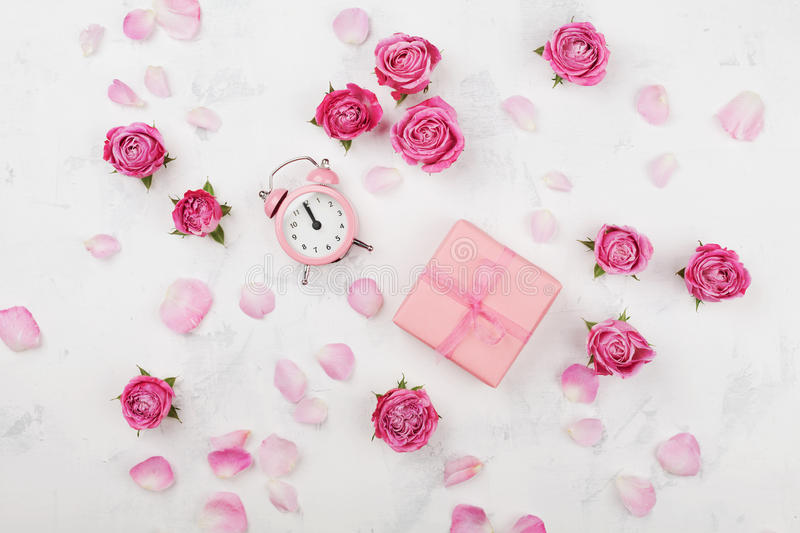 Gift box, alarm clock, petals and pink rose flowers on white table top view in flat lay style. Greeting for Mother or Woman day stock photos