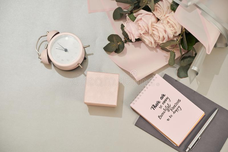 Gift box, alarm clock and pink rose flowers on white table top view in flat lay style. Greeting card for Mother or Woman day royalty free stock image