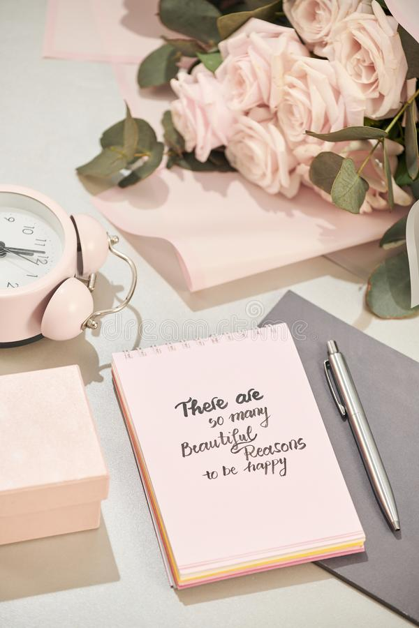 Gift box, alarm clock and pink rose flowers on white table royalty free stock images