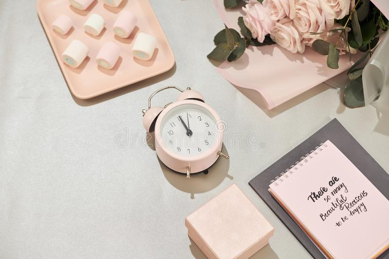 Gift box, alarm clock and pink rose flowers on white table stock photo
