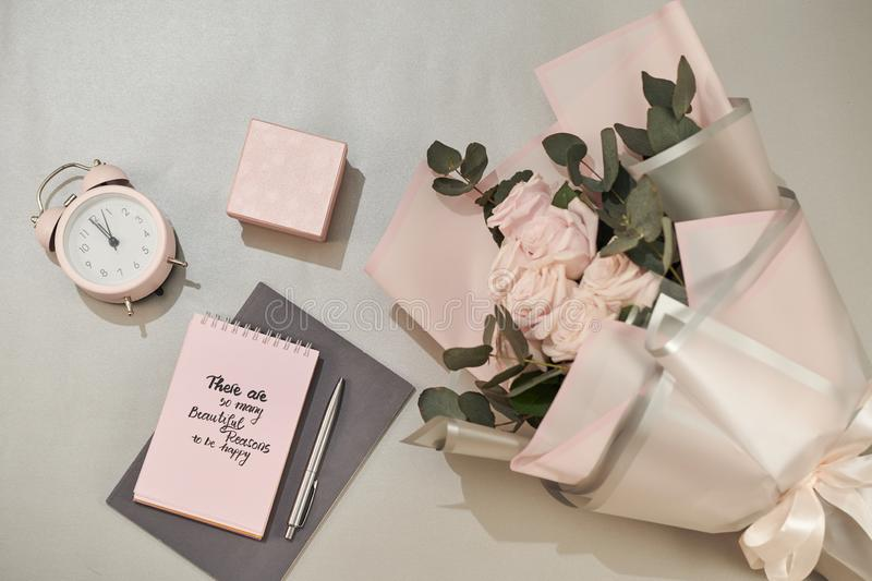 Gift box, alarm clock and pink rose flowers on white table top view in flat lay style. Greeting card for Mother or Woman day royalty free stock photos