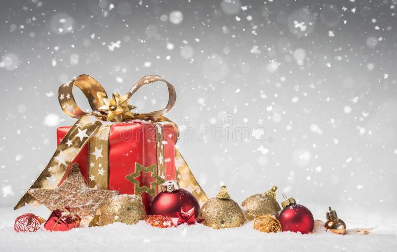 Gift Box and Baubles on Snow with falling Snowflakes - Christmas Background - Voucher stock images