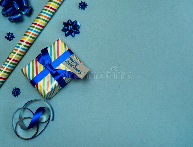 Gift box in beautiful packaging, gift wrapping paper, bows and ribbon on a blue-gray background. royalty free stock photos