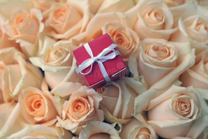 Gift box on beautiful roses background stock photos