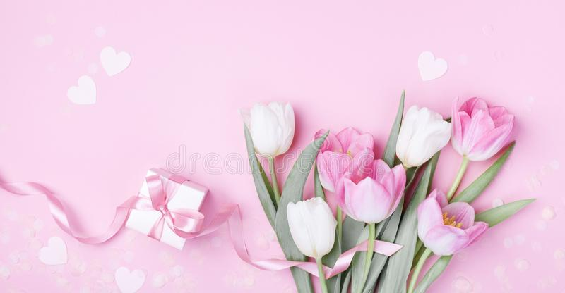 Gift box and beautiful spring tulip flowers on pastel pink background. Banner for Women Day, Mother day. Flat lay. Style stock images