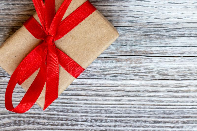 A gift box, beautifully wrapped with kraft paper and red ribbon and large bow on wooden background with copy space royalty free stock images