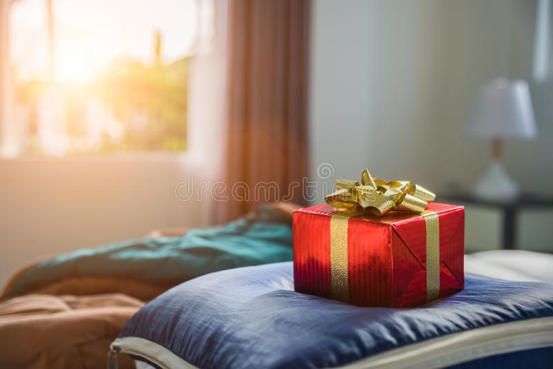 Gift box in bedroom. Holiday and anniversary day concept. Birthday and Valentines day surprise concept. Chirstmas and New year th royalty free stock photos