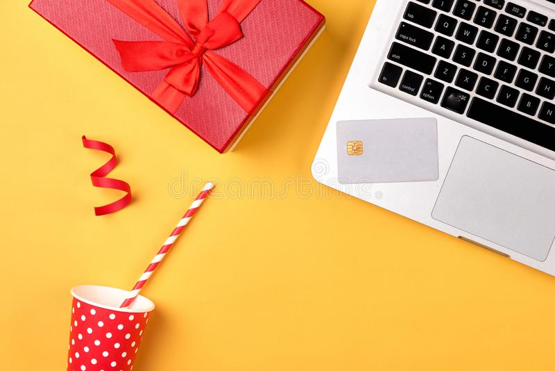 Gift box, birthday party things and laptop on a yellow background stock images