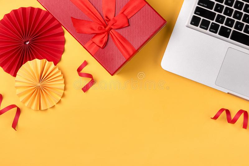 Gift box, birthday party things and laptop on a yellow background royalty free stock photo