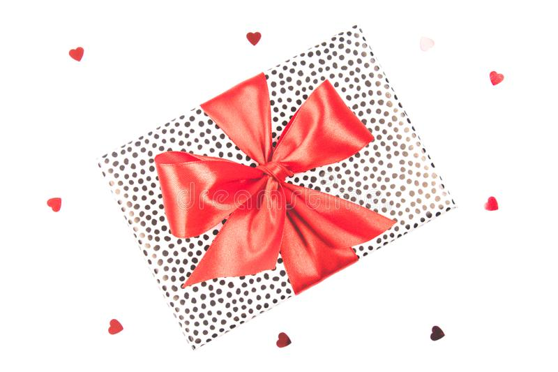 Gift box with black spots and red satin bow on a white background with glitter hearts. Festive concept royalty free stock images