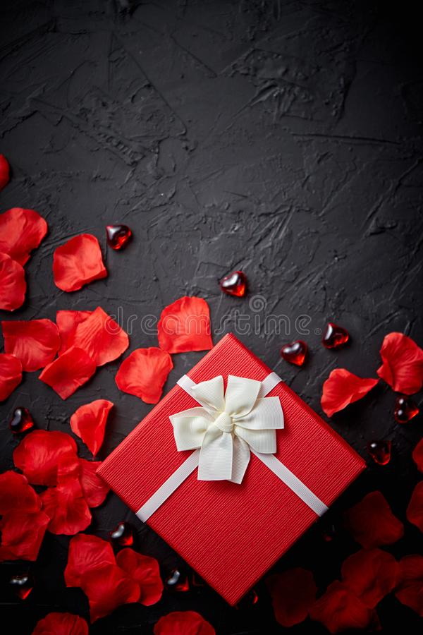Gift box on black stone table. Romantic holiday background with rose petals stock images