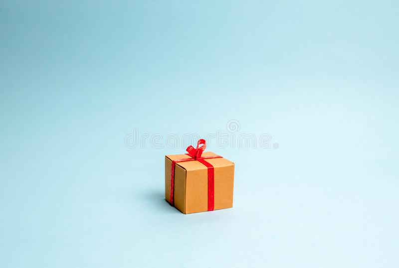 Gift box on blue background. Minimalism. The approach of the New Year holidays or birthday. Sale of gifts, special promotion royalty free stock image