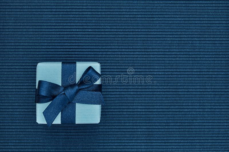 Gift box with bow on dark blue striped cardboard surface stock image