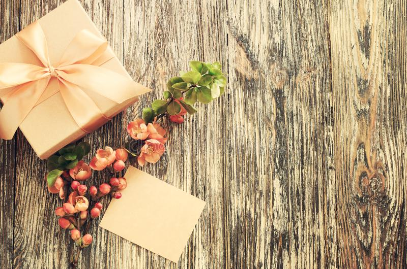 Gift box with bow ribbon, blank tag and delicate flowering branch stock photography