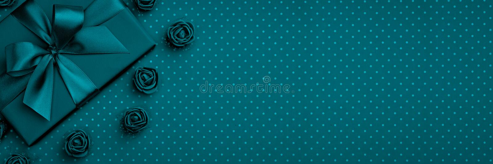 Gift box with bow and ribbon, flower rose top view on dark blue or turquoise background. Flat lay. Top View. 8 march Womens Day stock image