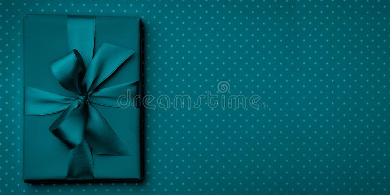 Gift box with bow and ribbon top view on dark blue or turquoise background. Flat lay. Top View. 8 march Womens Day, Birthday. Gift box with bow and ribbon royalty free stock photo