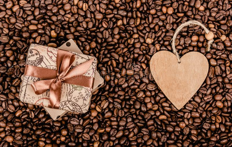 Gift box with bow and Valentine. Gift box with ribbon and wooden heart. Coffee background and gift. royalty free stock image