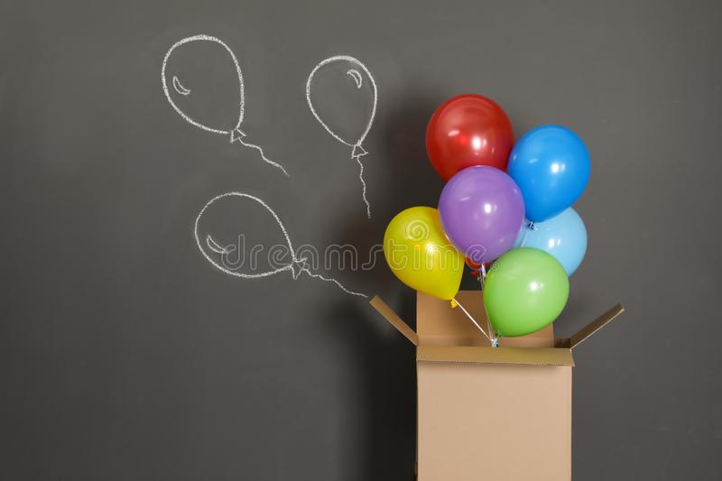 Gift box with bright air balloons and chalk drawing on background royalty free stock photo