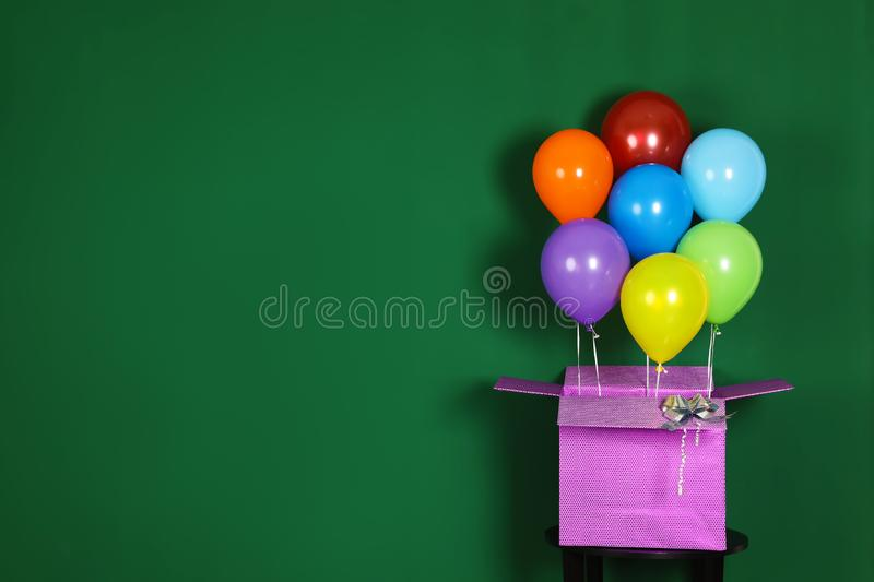 Gift box with bright air balloons on green background royalty free stock photo