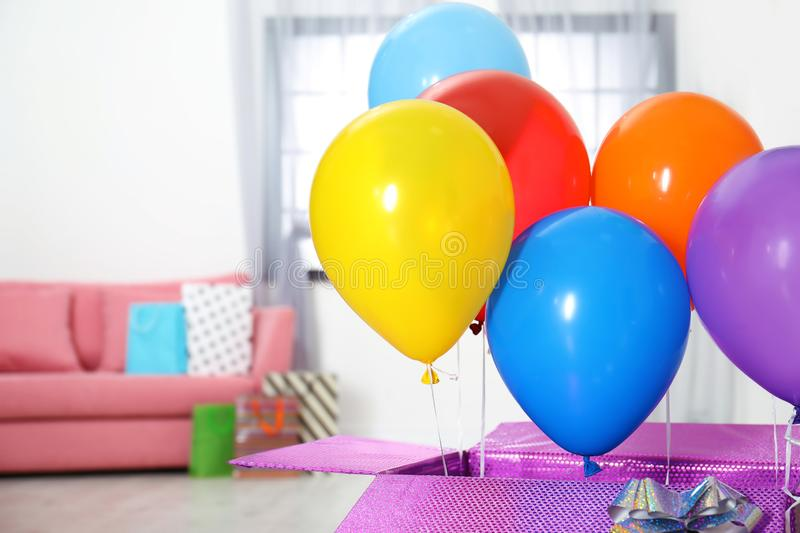 Gift box with bright air balloons in living room. royalty free stock photos