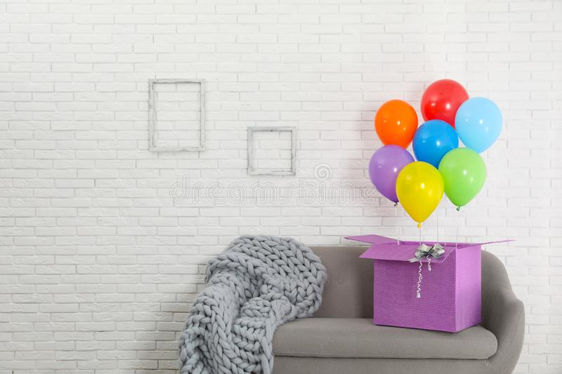 Gift box with bright air balloons on sofa against white wall. Space for text royalty free stock photo