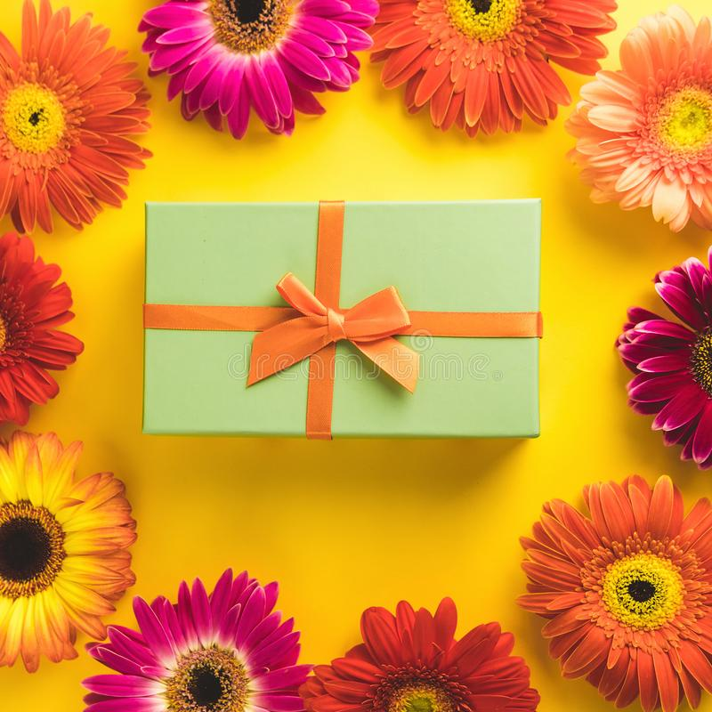 Gift box with bright beautiful gerbera flower on sunny yellow background. The concept of the New Year, Christmas royalty free stock photo